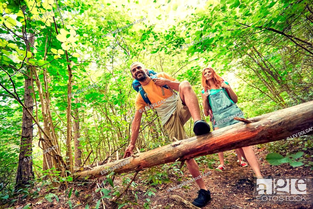 Stock Photo: adventure, travel, tourism, hike and people concept - group of smiling friends walking with backpacks in woods.