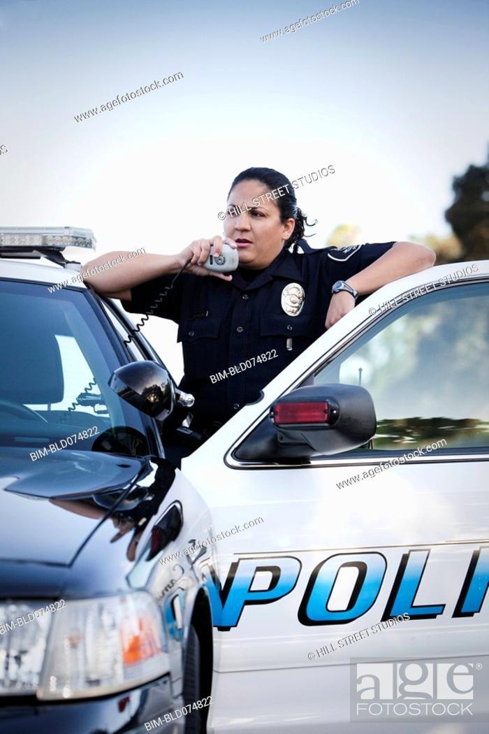 Stock Photo: Hispanic policewoman talking on CB radio.