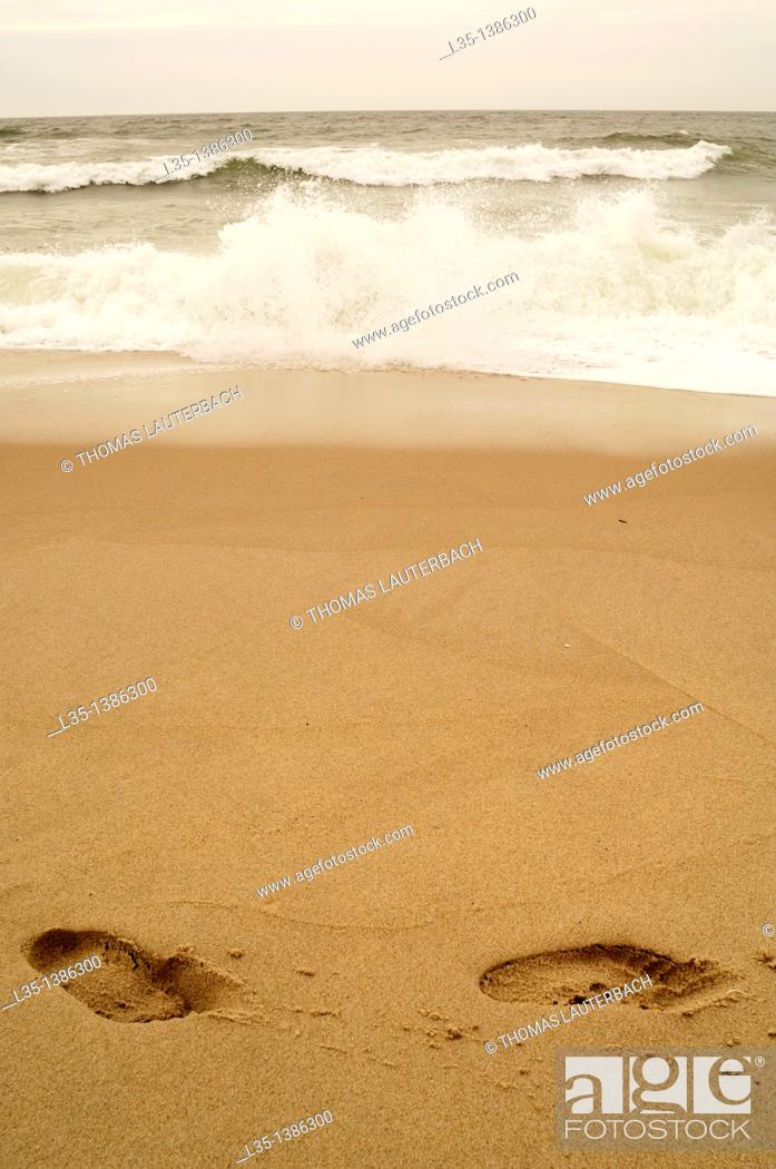 Stock Photo: Two footprints in the sand with sea spray from waves.