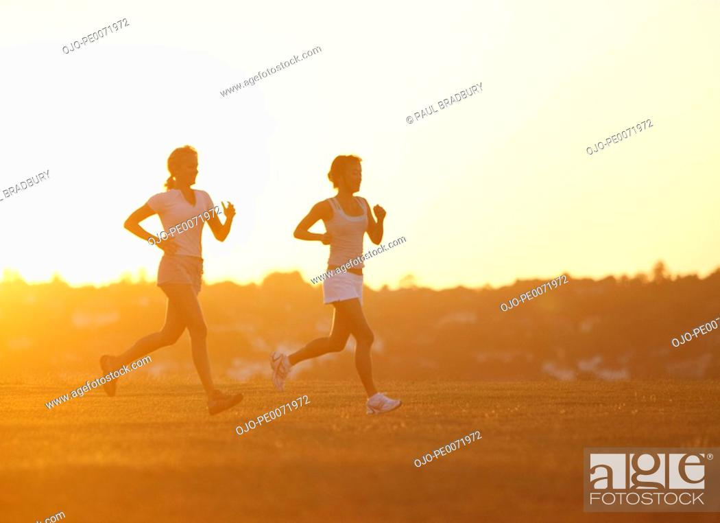 Stock Photo: Women running through field.