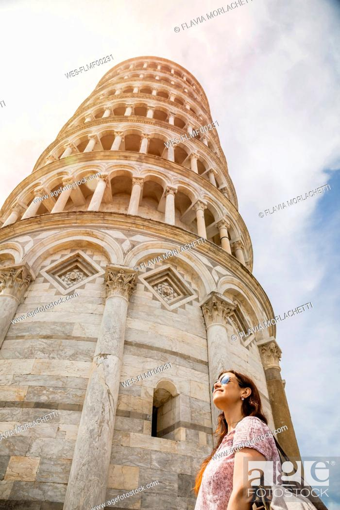Stock Photo: Female tourist looking at Leaning Tower of Pisa against sky, Pisa, Tuscany, Italy.