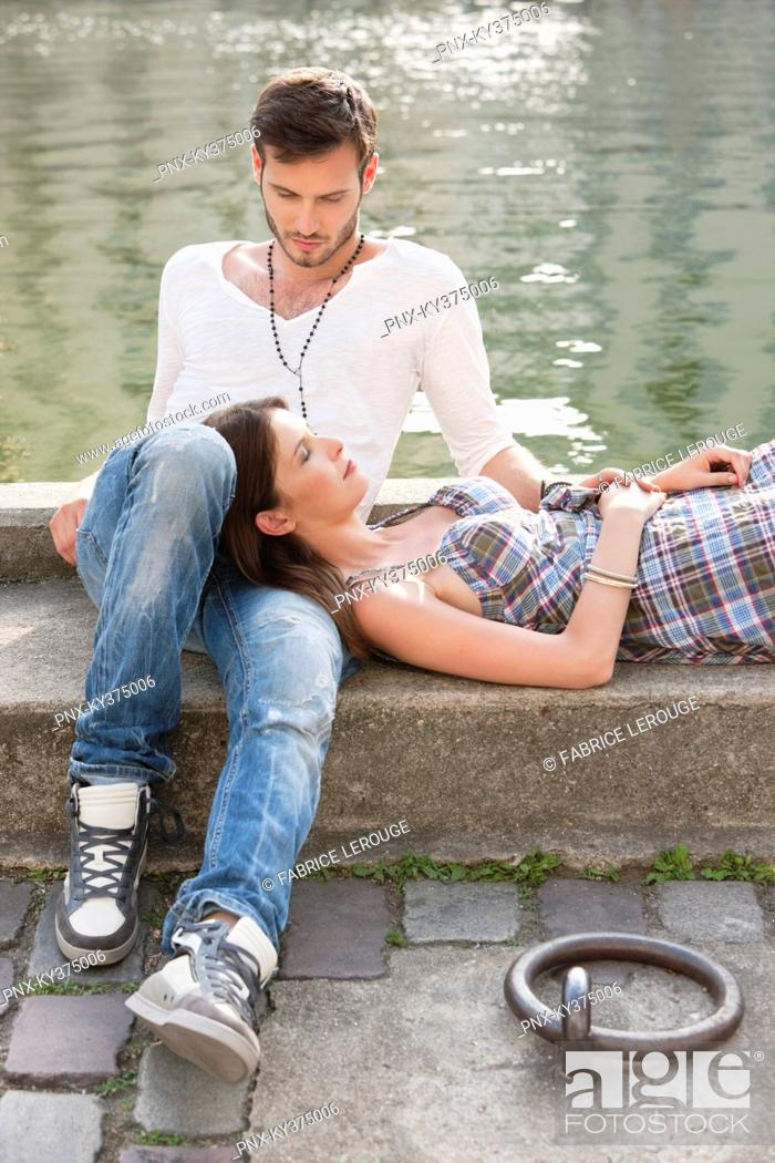 Stock Photo: Woman lying on lap of a man at the ledge of a canal, Paris, Ile-de-France, France.