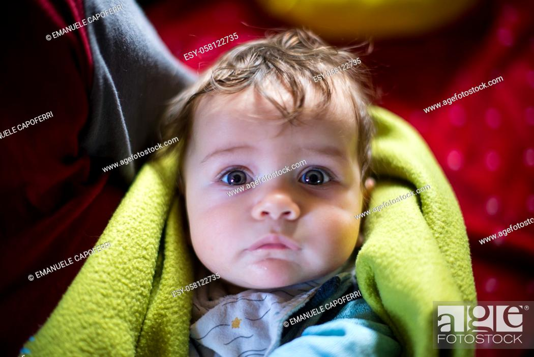 Imagen: portrait of 5 month old baby wrapped in blanket in mother's arms.