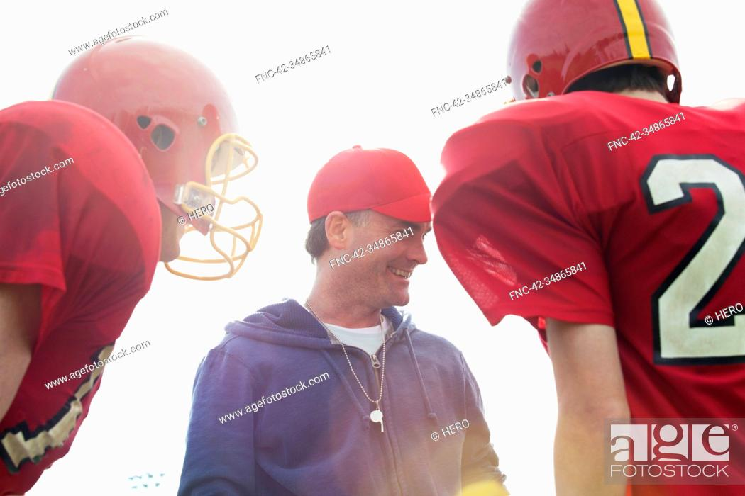 Stock Photo: Coach talking with college football players.