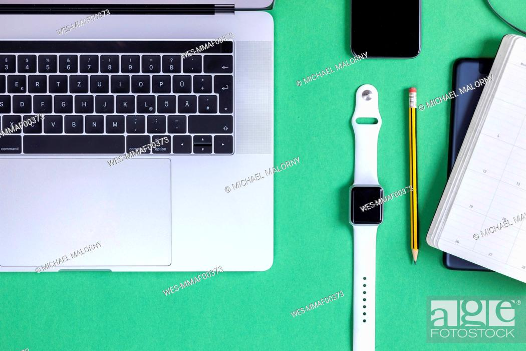 Stock Photo: Business desk in front of green background seen from above.