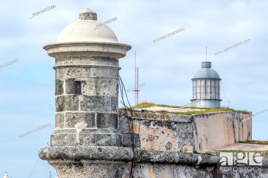 Stock Photo: Faro Castillo del Morro peeking up behind a tower of Morro Castle , Havana, Cuba.
