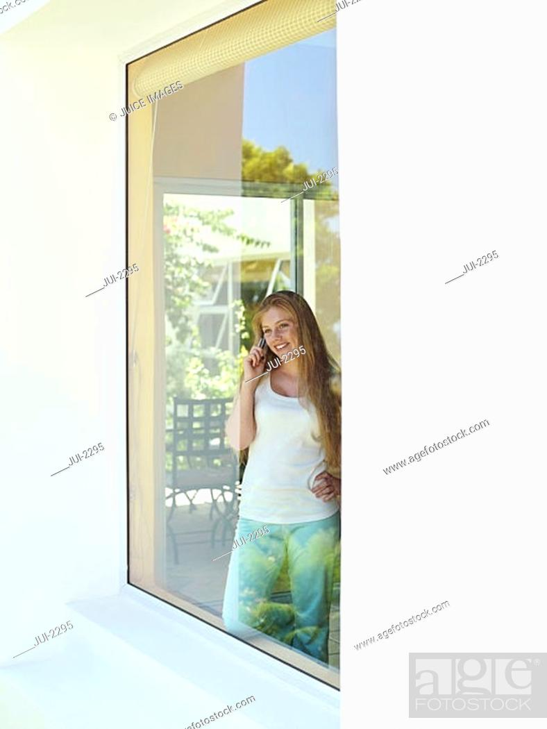 Stock Photo: Teenage girl 15-17 looking through window at home, using mobile phone, smiling.