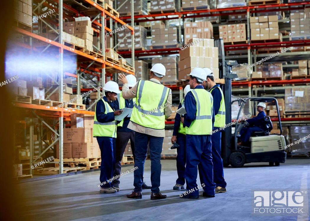 Stock Photo: Manager and workers meeting in distribution warehouse.