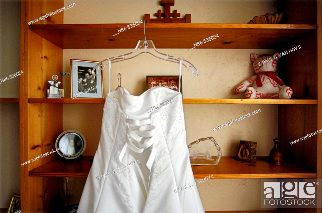 Stock Photo: Bridal gown hanging on shelves.