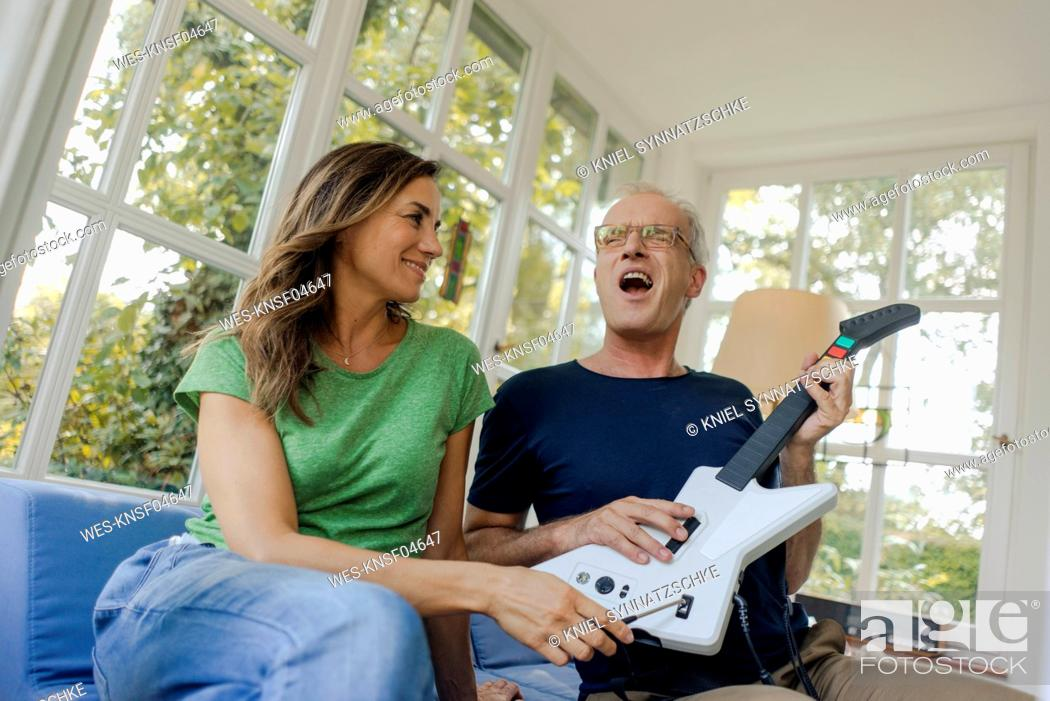 Imagen: Happy mature couple sitting on couch at home with toy electric guitar.