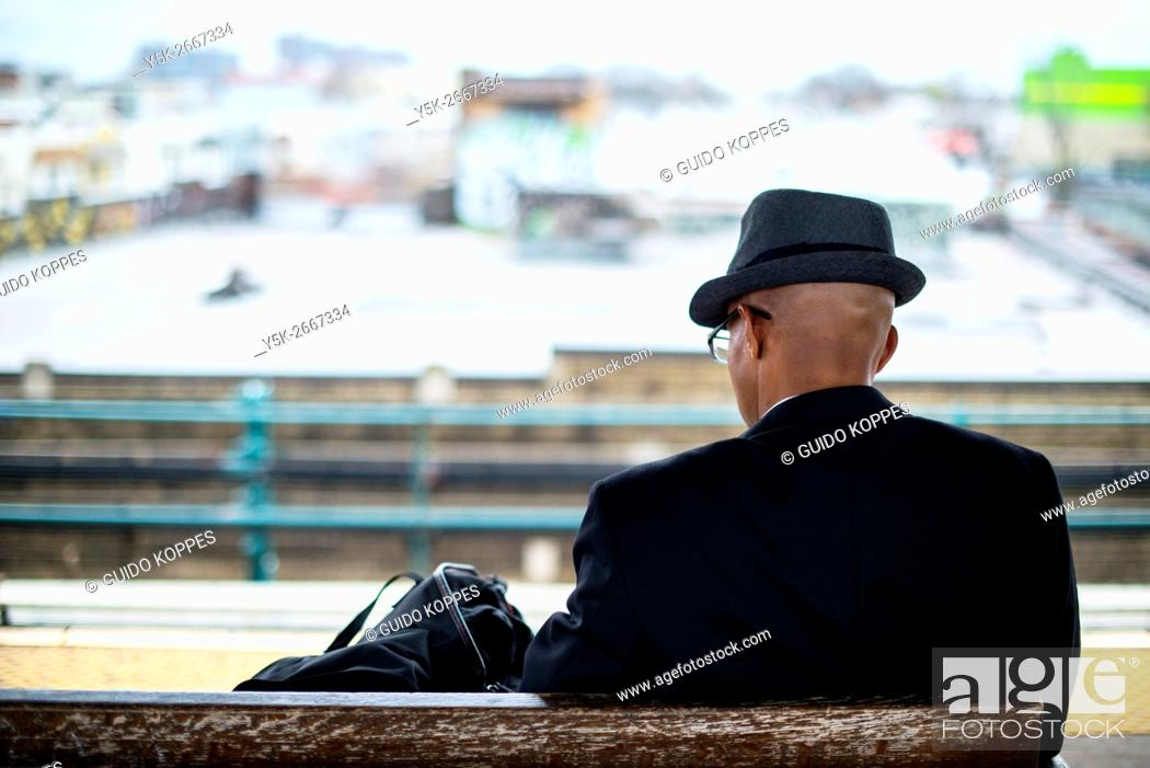 Stock Photo: New York City, USA. African-American male, wearing a had and coat, sitting on a subway station plafrom bench, while waiting for his subway train to JFK Airport.