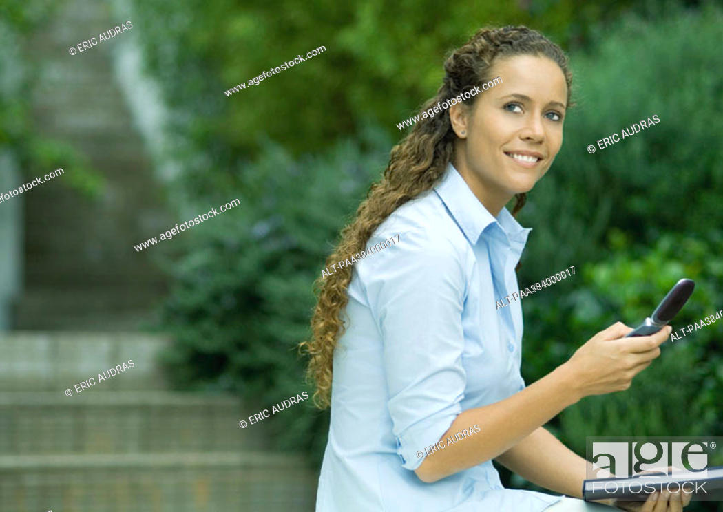 Stock Photo: Woman using cell phone outdoors, holding agenda.