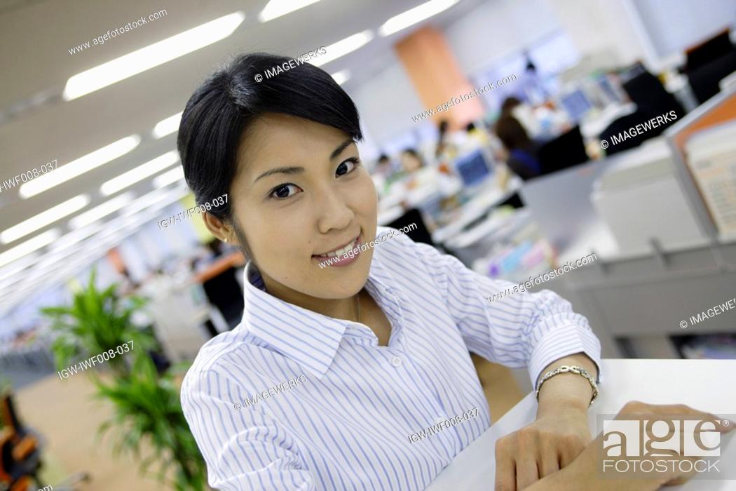 Stock Photo: A woman sitting in her office smiles at the camera.