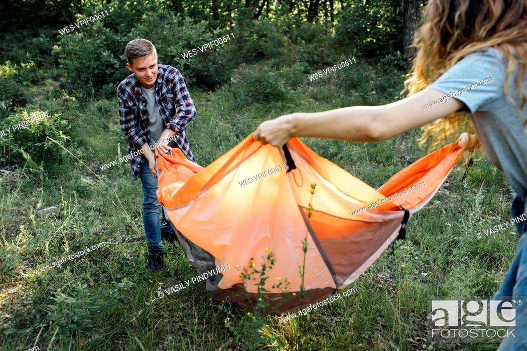 Photo de stock: Young couple camping in nature, setting up tent.