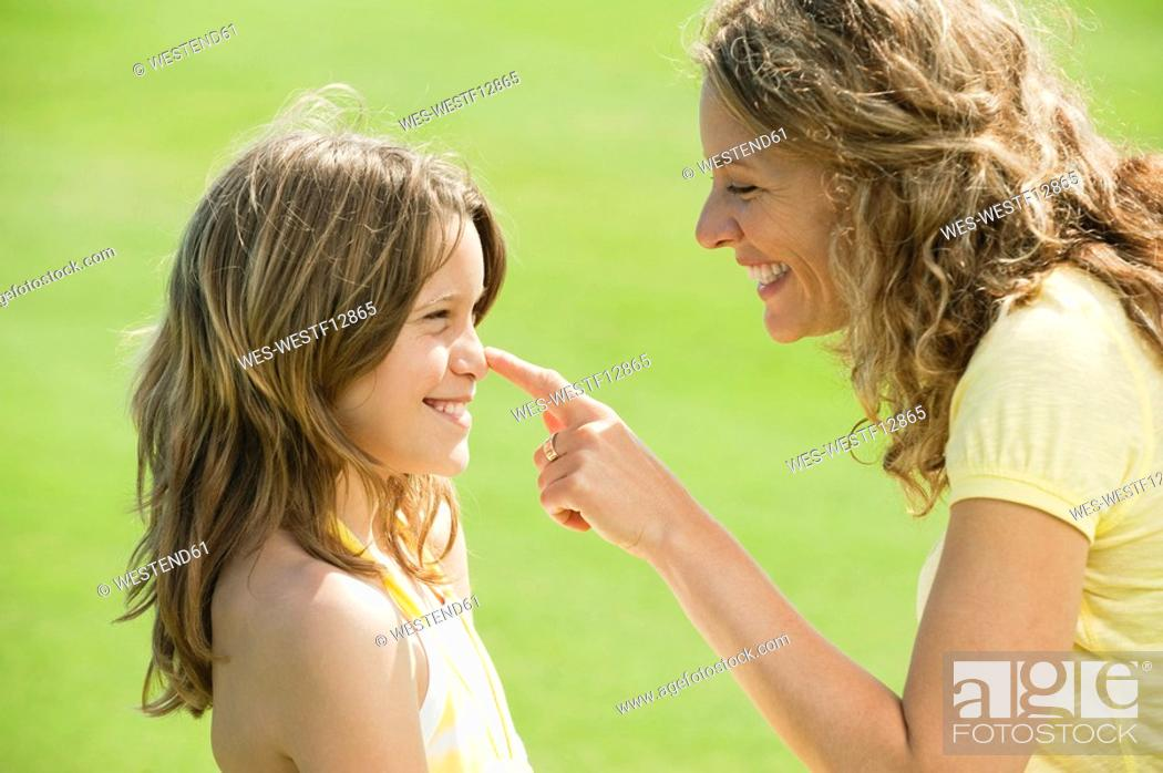 Stock Photo: Spain, Mallorca, Mother touching daughter's 10-11 nose, smiling, side view, portrait.