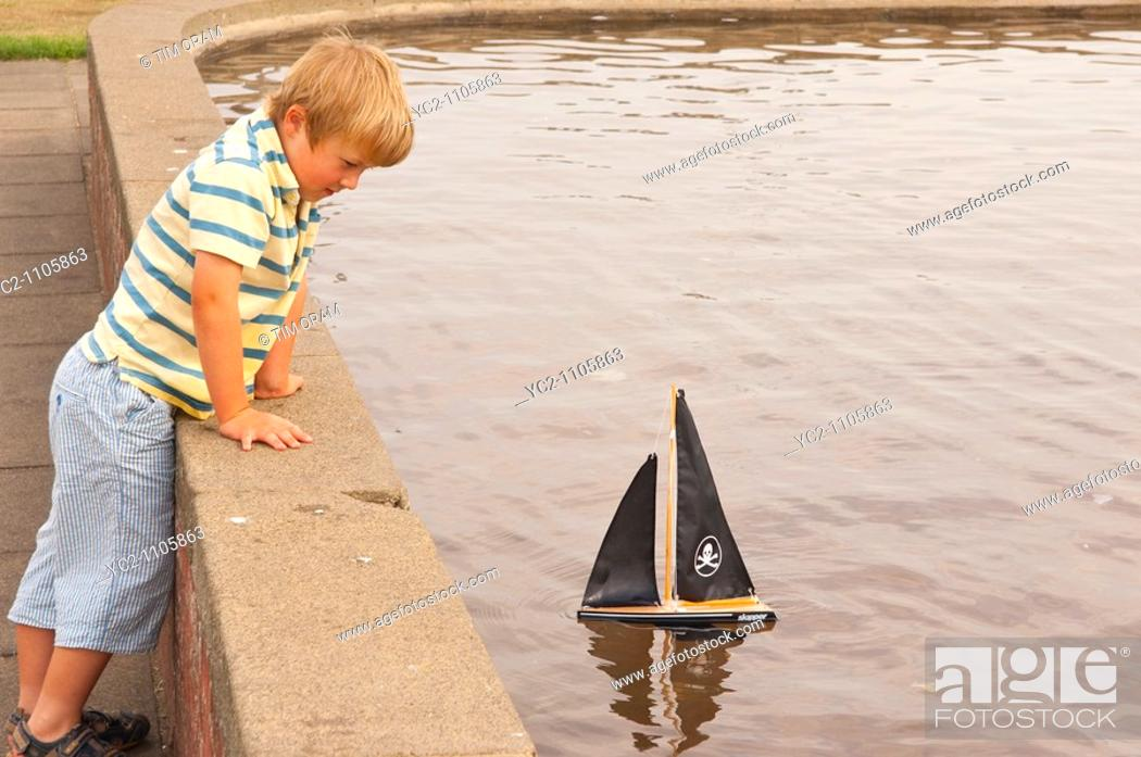 Stock Photo: A small boy sailing his toy boat at the boating lake in Aldeburgh , Suffolk , Uk.