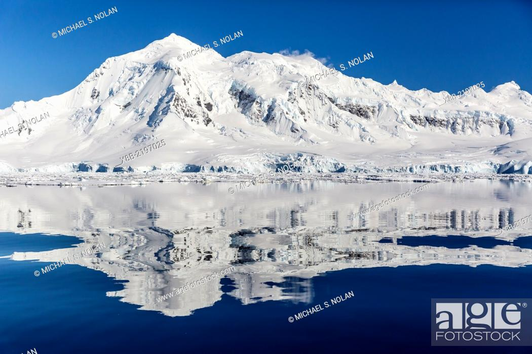 Imagen: Snow-capped mountains reflected in the Neumayer Channel near Port Lockroy, Antarctica.
