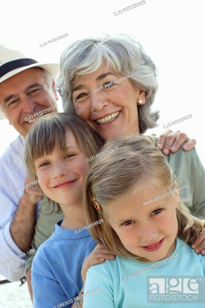 Stock Photo: Couple and two young kids outdoors looking at camera.