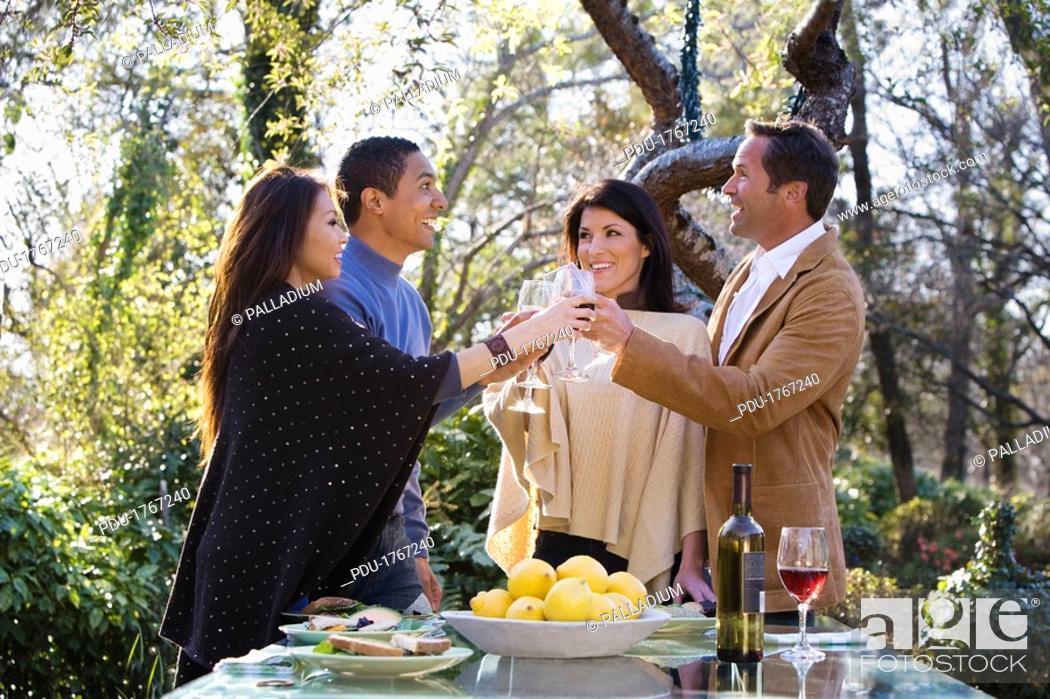 Stock Photo: Friends having drinks at outdoor dinner party.
