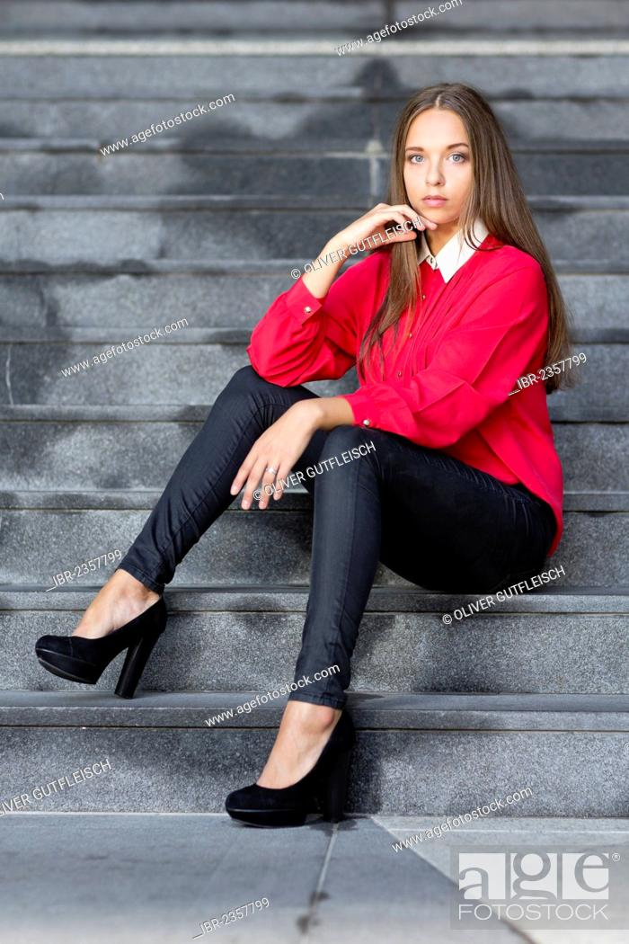1308e861bfa661 Stock Photo - Young woman wearing a red top, black trousers and high black  shoes posing while sitting on stairs