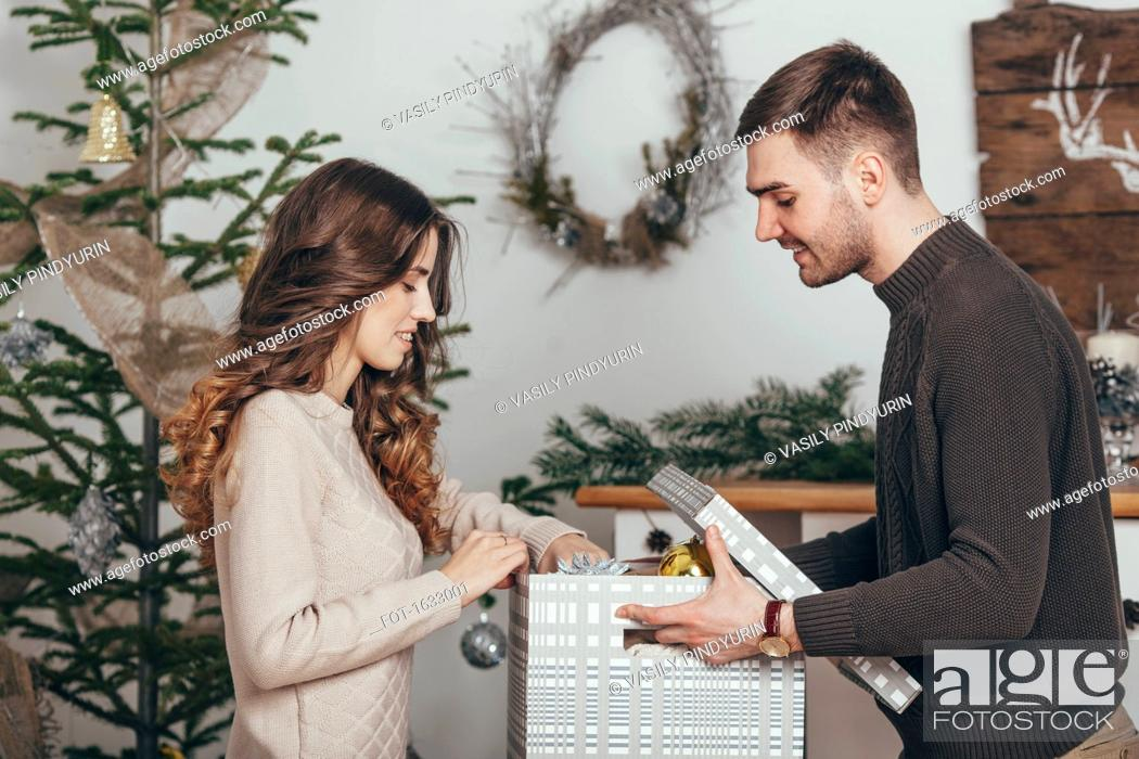 Stock Photo: Side view of smiling couple packing Christmas gifts at home.