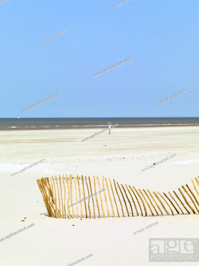 Stock Photo: A slanting fence on a beach and the sea in the background.