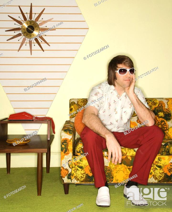 Stock Photo: Caucasian mid-adult man wearing sunglasses sitting on colorful retro sofa looking bored.
