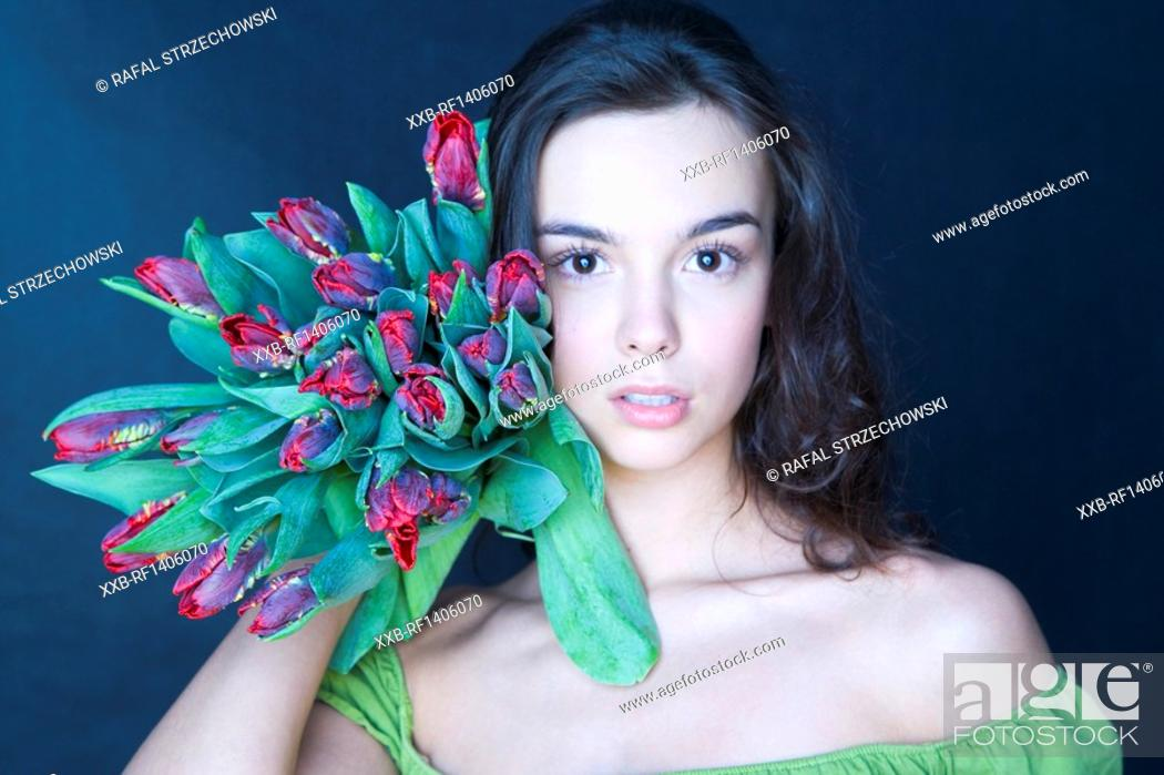 Stock Photo: young woman with banch of tulips.
