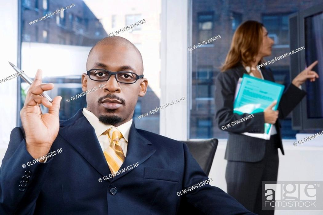 Stock Photo: Portrait of a businessman thinking with a businesswoman standing in the background.