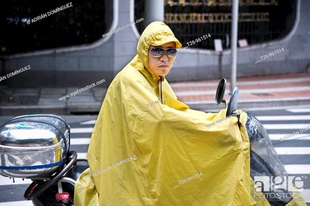 Stock Photo: a man on a motorcycle with raincoat. Shanghai, China.