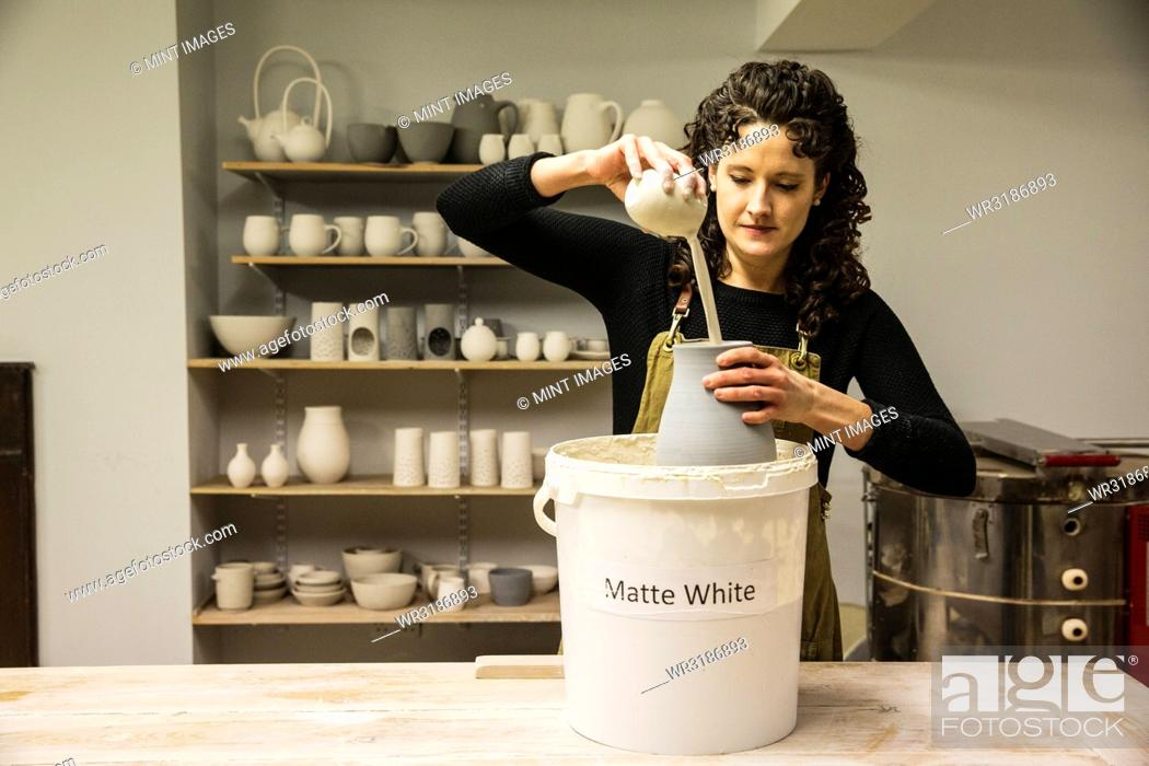 Stock Photo: Woman with curly brown hair wearing apron standing in pottery workshop, pouring white glaze over unfired vase.