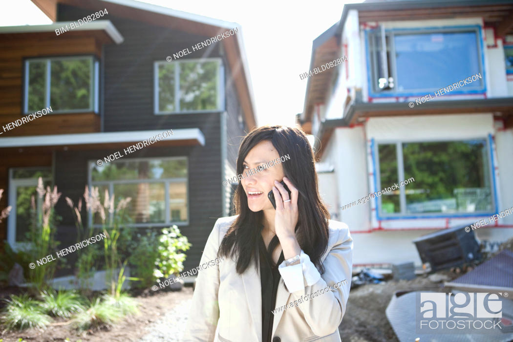 Stock Photo: Mixed race real estate agent standing near house talking on cell phone.