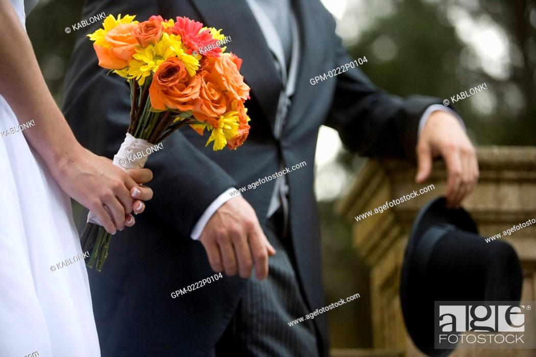 Stock Photo: Close-up of midsection of bride and groom holding bouquet and hat.