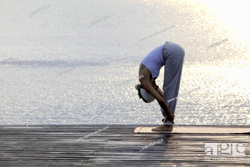 Stock Photo: Woman doing yoga exercise on a jetty at a lake, Munich, Bavaria, Germany.