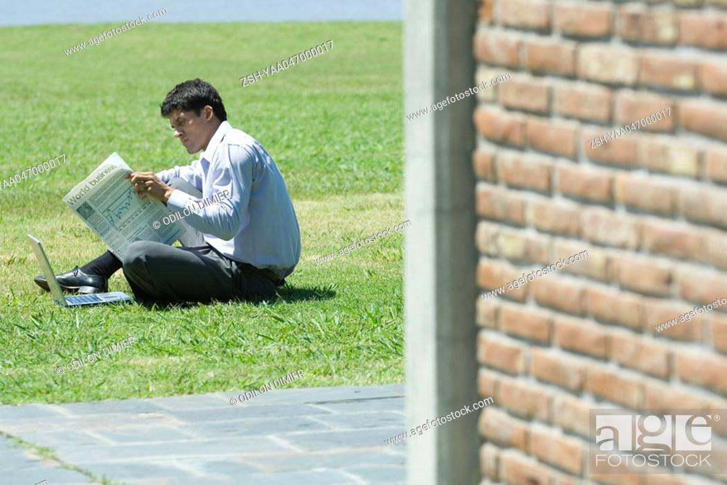 Stock Photo: Businessman sitting on ground with laptop, reading newspaper.