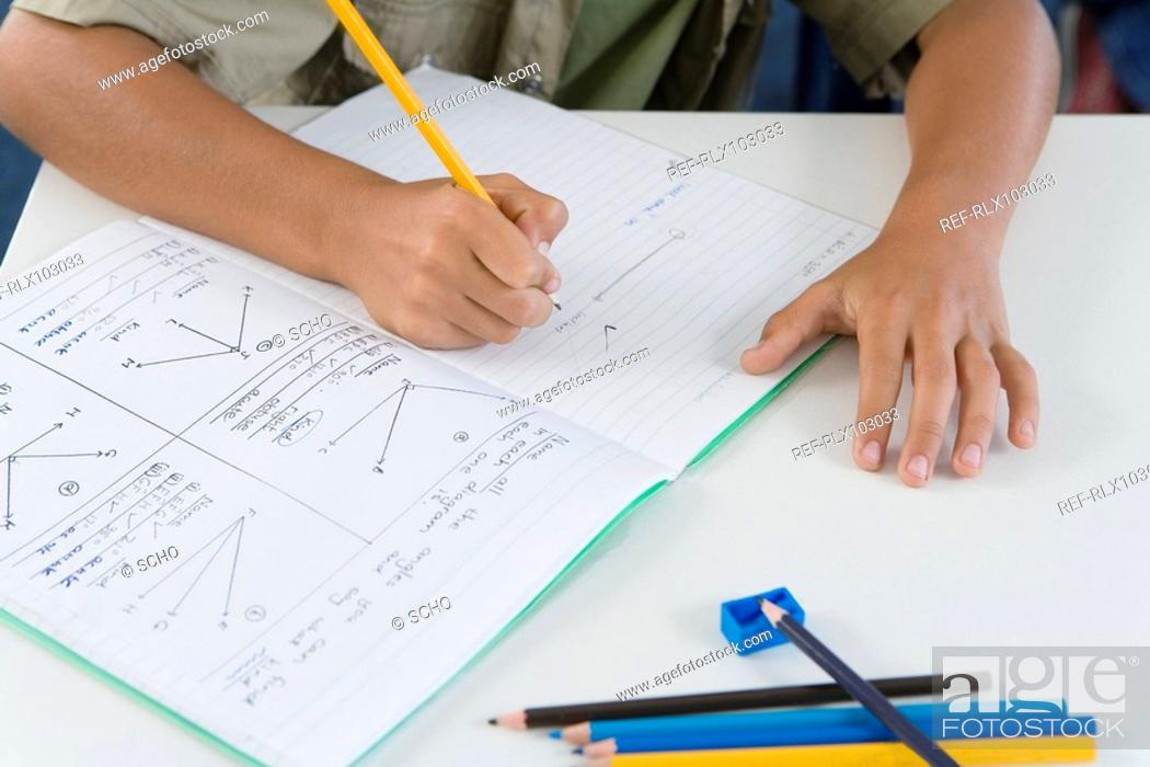 Stock Photo: School boy 10-13 writing in classroom, close-up, detail.