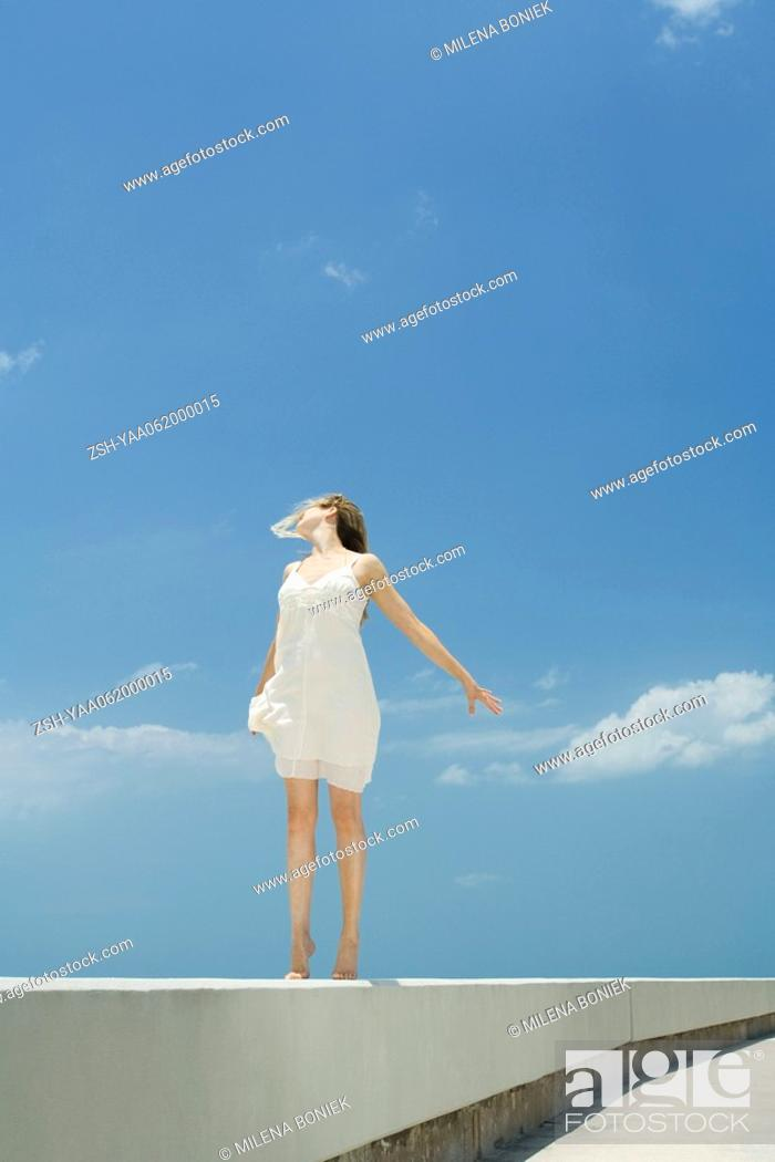 Stock Photo: Young woman standing on tiptoe on low wall, arms out, head back.