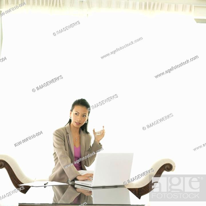 Stock Photo: Businesswoman holding a glass of water.
