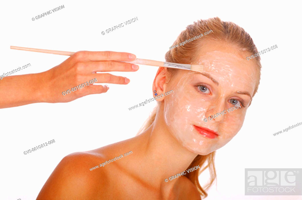 Stock Photo: Hand putting a face pack on a woman's face with a brush.