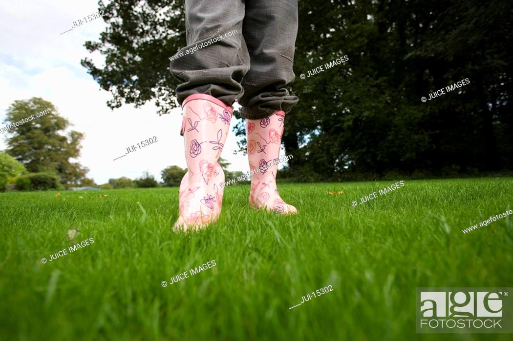 Photo de stock: Girl 8-10 in wellington boots on grass, low section.