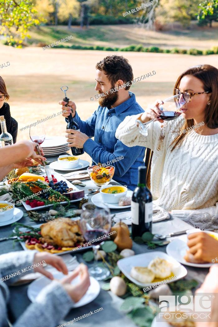 Stock Photo: Friends eating at outdoor table.