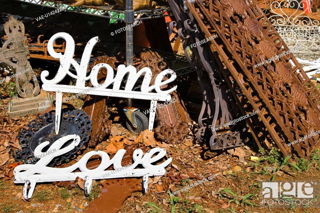 Stock Photo: Metal garden decorations of words Love and Home next to rusted metal objects.