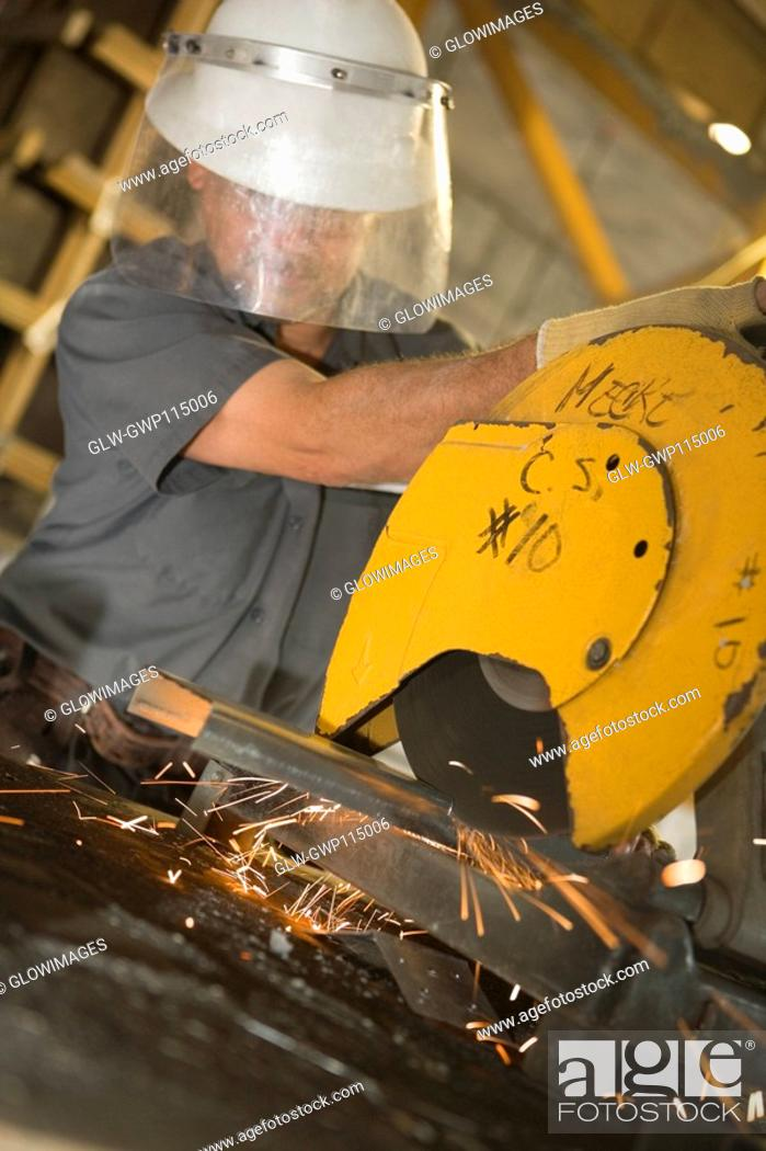 Stock Photo: Male construction worker working on an electric saw at a construction site.