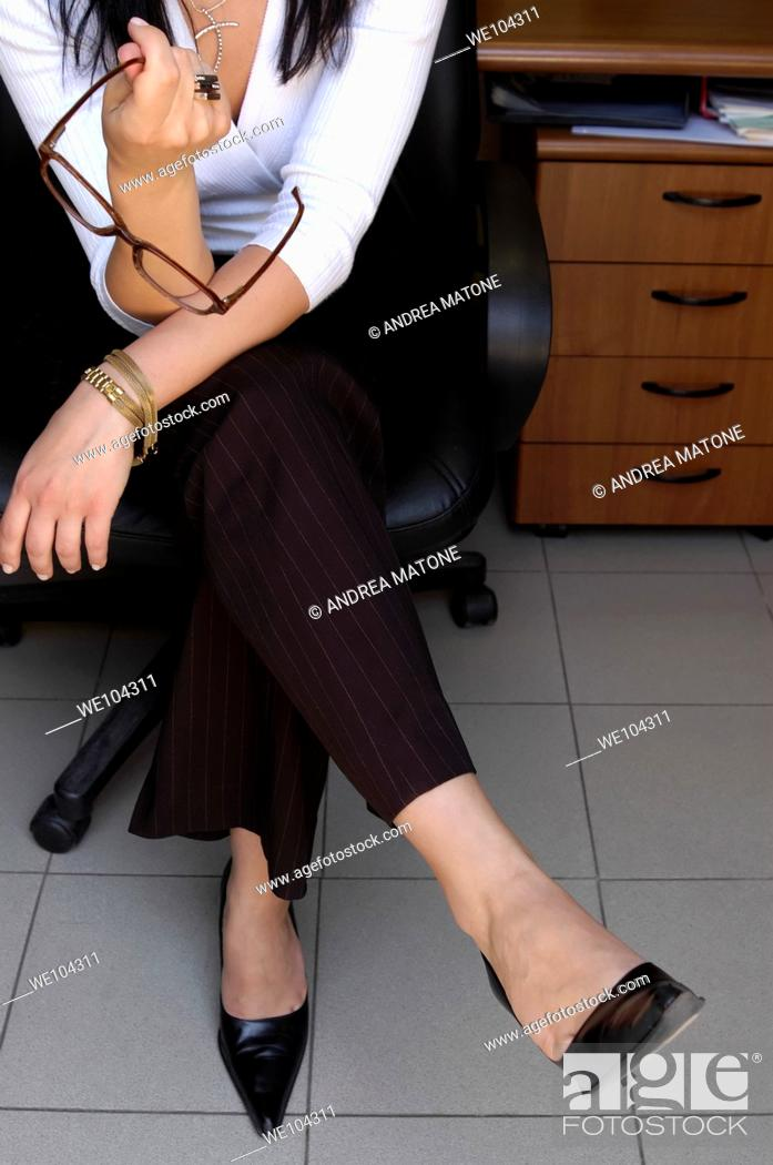 Stock Photo: Businesswoman portrait holding glasses at desk business office Rome Italy.