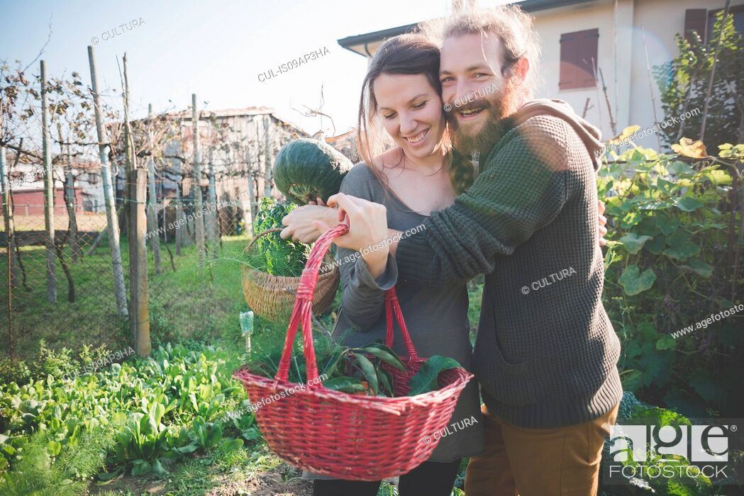 Imagen: Young couple with basket of homegrown vegetables.