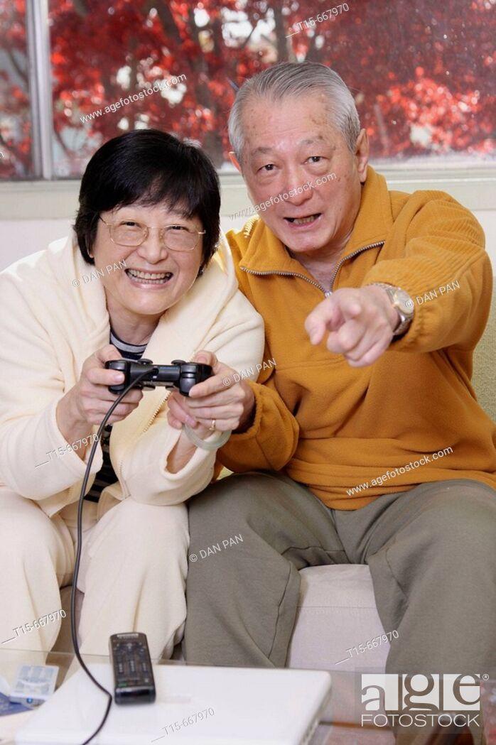 Stock Photo: Senior Asian couple having fun playing video playstation games on tv.