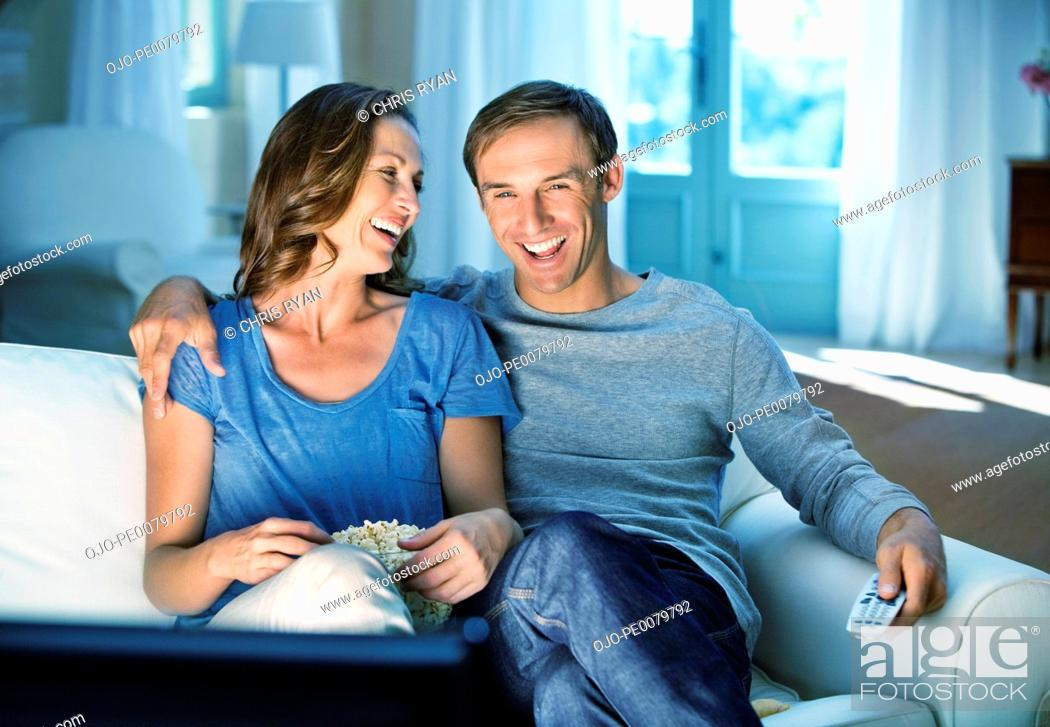 Stock Photo: Happy couple watching TV on sofa.