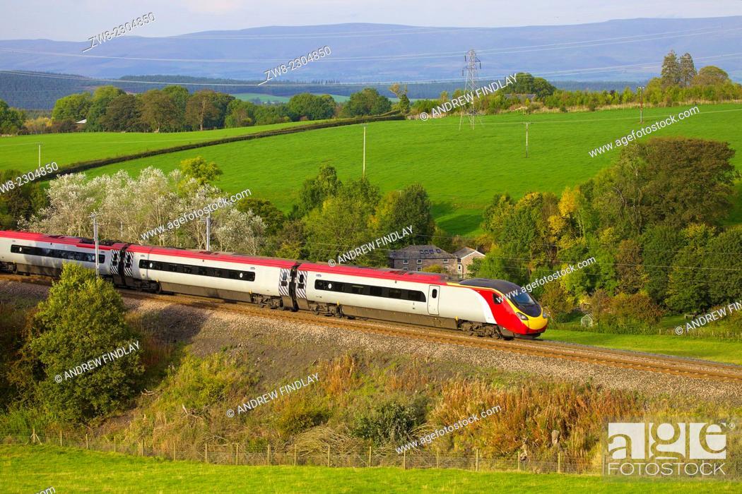 Stock Photo: Class 390 Pendolino Virgin train passing Strickland Mill, Great Strickland, Cumbria, West Coast Main Line, England, UK.