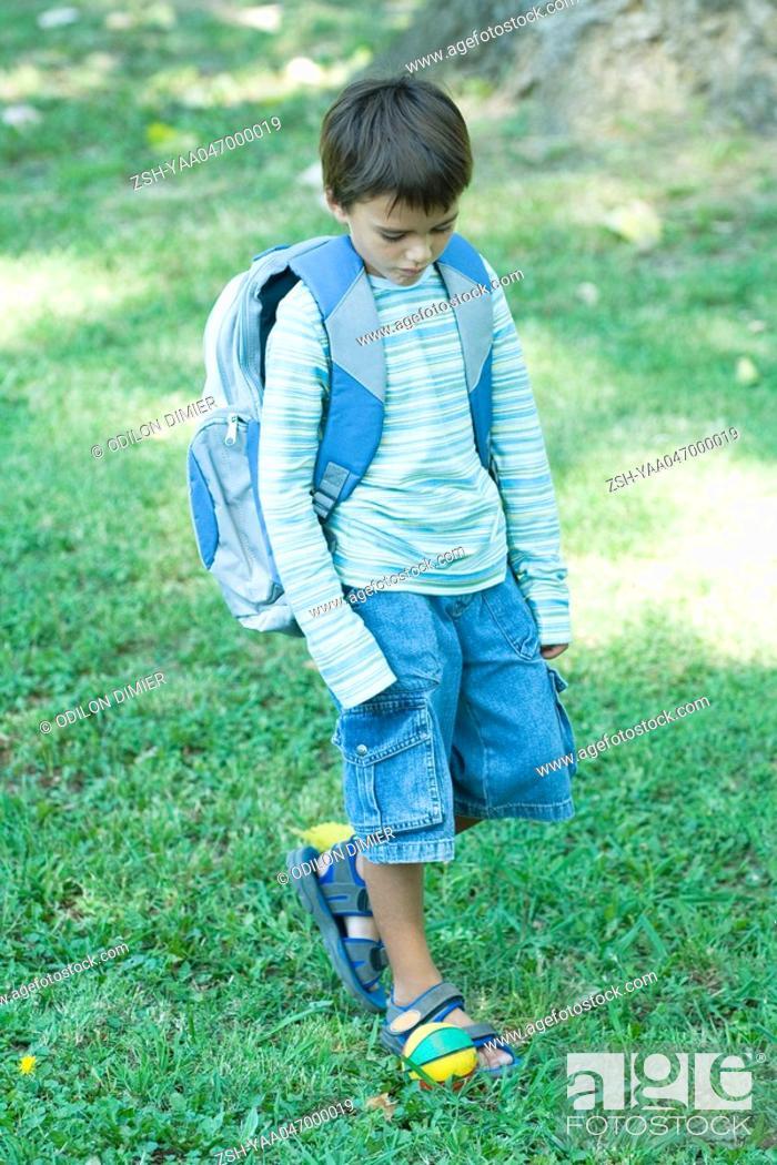 Stock Photo: Boy walking across grass wearing backpack.