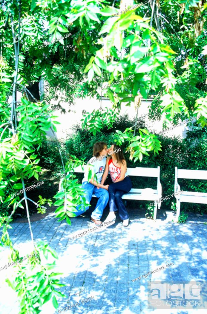 Stock Photo: Young couples kissing on a park bench.
